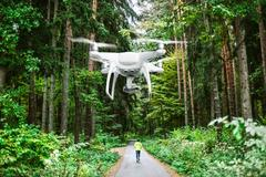 Hovering drone taking pictures of man running in forest Kuvituskuvat