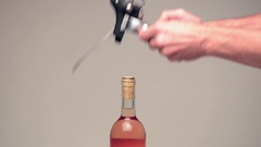 Closeup of a man hand using modern metal cork screw for pulling the cork Stock Footage