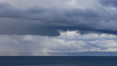 Stormy clouds over calm blue sea Stock Footage
