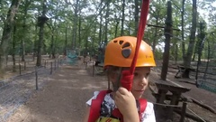 A little girl wearing helmet  going down on the pulley in the adventure pa Stock Footage