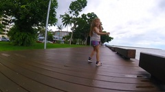 A little girl running on the esplanade, a kind of wooden waterfront in Aus Stock Footage