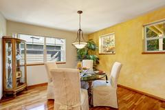 Interior of dining room with yellow contrast wall and hardwood floor. Stock Photos
