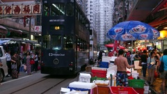 HONG KONG - Evening view of wet market with people and double-decker trams. 4K Stock Footage