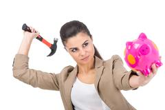 Young woman is going to smash piggy bank with a hammer, isolated on white backgr Stock Photos