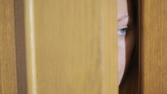 Girl spies through a door crack. Eye looking through a slit Stock Footage