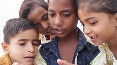 Indian kids sharing a touch screen phone mobile screen, handheld Stock Footage