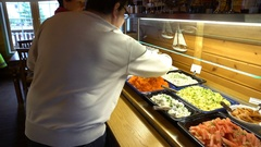 The restaurant guests select food from a buffet. Dolly shot. Stock Footage