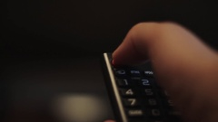 Human hand is pressing button on black TV remote control Stock Footage