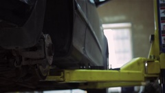 Low section of male mechanic repairing car's tire in repair shop Stock Footage