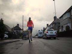 4k Girl Running in rain, Northampton suburbs Gimbal Shot Stock Footage