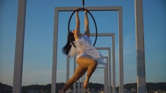 Air gymnastics woman performs acrobatics tricks on aerial hoop Stock Footage