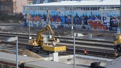 Earthmover on railroad train tracks moves soil, construction workers, Berlin Stock Footage