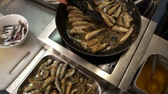 Cook roasts fresh smelt in the fish restaurant. Close-up. Stock Footage