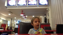 Child in cafe plays with a knife Stock Footage