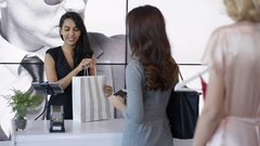 4K Woman shopping in clothing store makes contactless payment with cell phone Stock Footage
