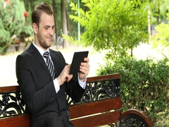 Happy Successful Businessman Using Digital Tablet Navigate Internet Park Bench Stock Footage