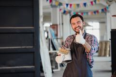 Handyman using brush in his workshop with thumb up Stock Photos