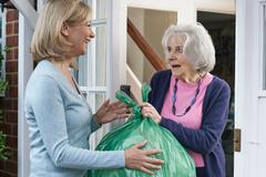 Woman Taking Out Trash For Elderly Neighbour Stock Photos