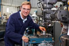 Portrait Of Engineer Using Drill In Factory Stock Photos