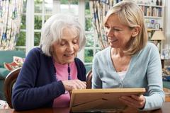 Senior Woman Looks At Photo In Frame With Mature Female Neighbor Stock Photos