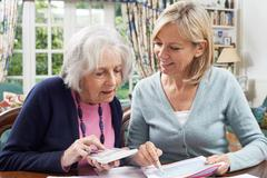 Female Neighbor Helping Senior Woman With Domestic Finances Stock Photos
