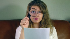 Pretty young woman using a magnifyer and enlarging an eye. Stock Footage