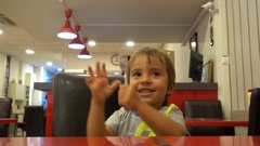 Kid plays with a fork and knife at cafe Stock Footage