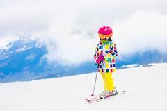 Ski and snow fun. Child in winter mountains. Stock Photos