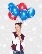 Happy teenage girl with helium balloons over snow Stock Photos
