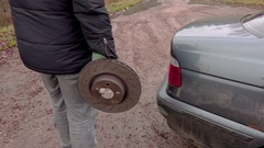 Man holding old brake disc near car Stock Footage