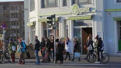 People cross street next to vegan Veganz supermarket, Berlin, Germany Stock Footage
