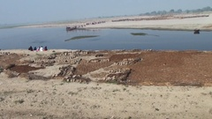 On the shore of the indian river Yamuna is drying the cow dung Stock Footage
