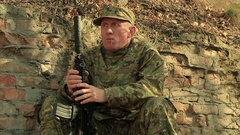 Adult Soldier with automatic rifle   chews  blade near  brick wall  Stock Footage