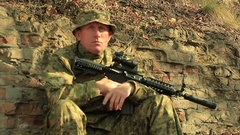 Adult Soldier with automatic rifle    sit near  brick wall  Stock Footage