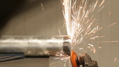 A worker using an angle grinder in a metal machine workshop Stock Footage