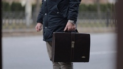 At the bus stop near the road a man with a briefcase expects public transport Stock Footage