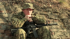 Adult  sad Soldier with automatic rifle    sit near  brick wall  Stock Footage