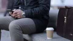 A man is typing a message on a smartphone. Hands close-up. Paper cup of coffee. Stock Footage