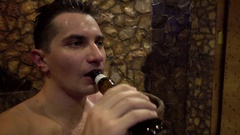 Man nude drinking beer in sauna Stock Footage