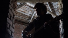 Young boy playing a guitar in the attic Stock Footage