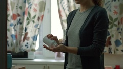 Taking pills with water- a young woman tips a couple of pills into her hand and Stock Footage