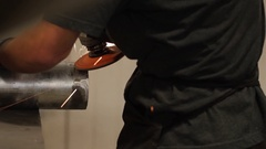 Worker uses an angle grinder in a metal machine workshop Stock Footage