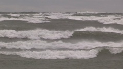 Hurricane force storm winds with waves crashing ashore and flooding beach Stock Footage
