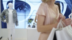 4K Young woman shopping in clothes store leaving the shop with lots of bags Stock Footage