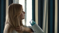Woman drying her hair in front of a mirror Stock Footage
