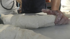 Pizzaiolos rolling and cutting dough in pizzeria Stock Footage