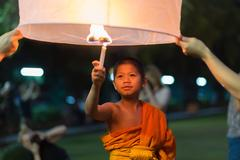 Young monk igniting floating lantern Stock Photos
