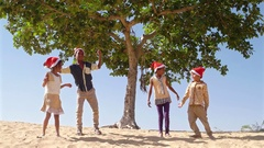 Wide shot of kids hugging embracing and huddling in sand desert with Santa hats  Stock Footage