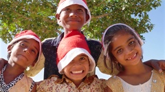 Kids having fun posing for camera with Santa hats with a tree in the backdrop  Stock Footage