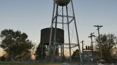 Tilt up-Old Milford Utah water tower with setting moon at sunrise Stock Footage